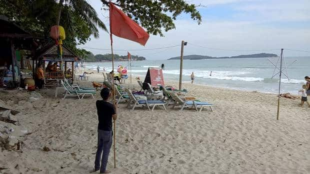 A man raises a red flag indicating rough weather conditions on Chaweng beach, Koh Samui, Thailand (Sithipong Charoenjai/AP)